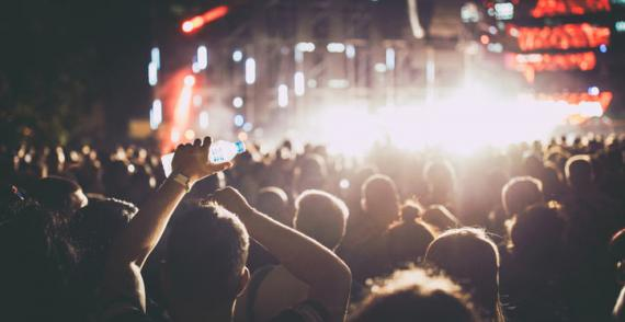 Person at festival with water bottle watches band from crowd at nighttime