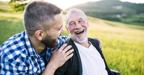 Man bonds with older man in wheelchair, laughing and looking to the future