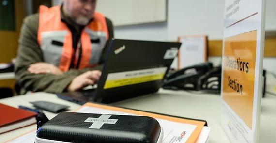 Man in logistics company office with naloxone kit on desk researches harm reduction