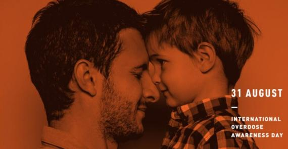 Father holds his young son, both are looking at eachother and smiling..
