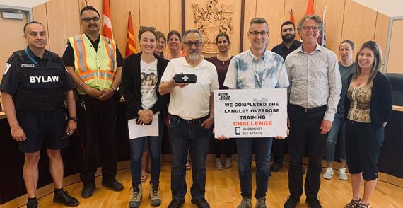 Group of bylaw officers and office workers smile after completing overdose prevention training