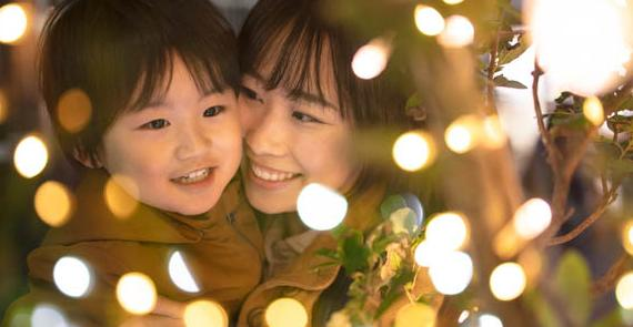 Mother and child enjoy looking at festive lights
