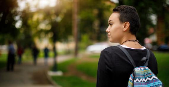 Young woman wearing a backpack looks optimistically into the distance