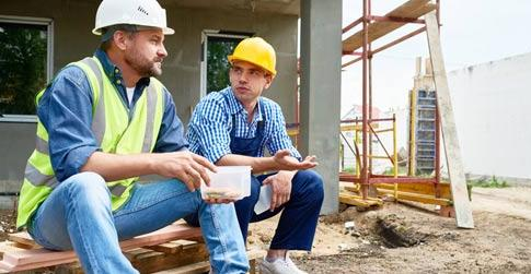 Two male construction workers discuss substance use during coffee break
