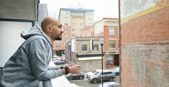 Man holds cup of coffee on balcony, thinking about men's mental health