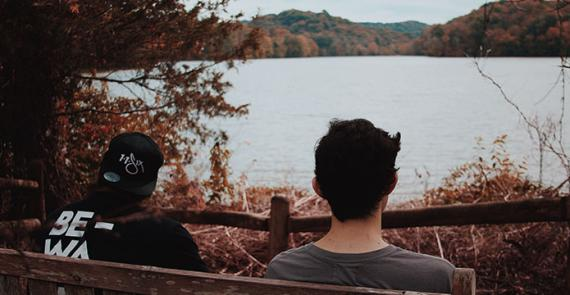 Two young men sat on a bench near a lake talking about substance use