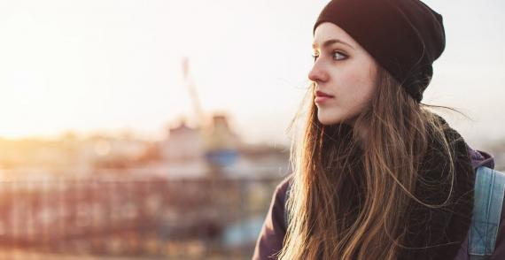 Young woman in downtown of a city looks off into the distance