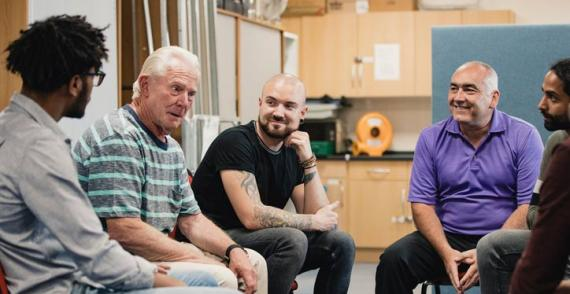 Men in support group talk about experiences positively and openly